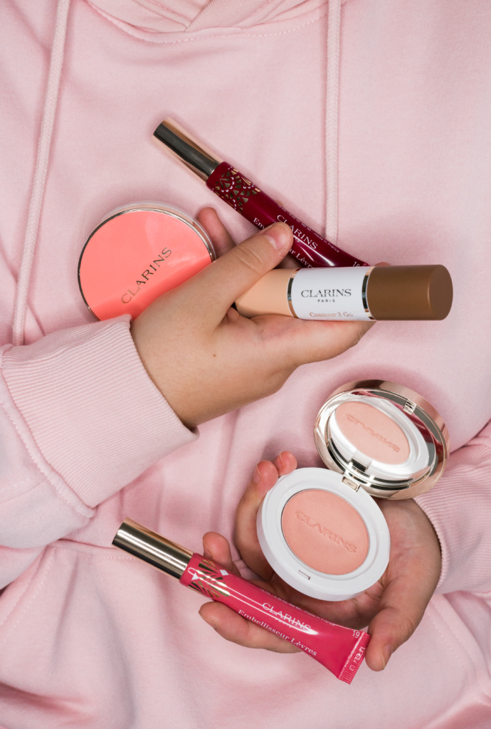 Claire holding Clarins makeup products
