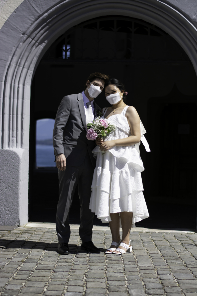 Claire and Nicolas wearing masks in front of the entry of Château de Nyon