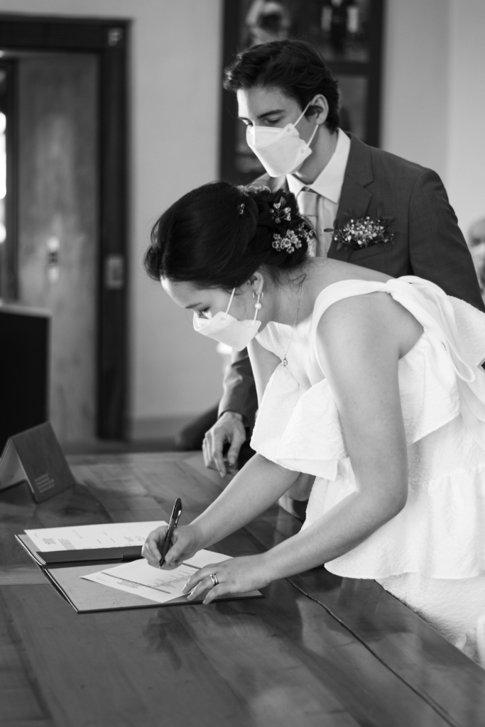 Claire signing administrative marriage forms during the civil ceremony