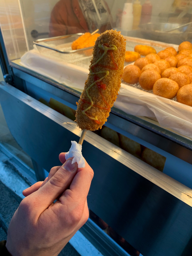 Corn dog on a stick with mustard and ketchup in Seoul
