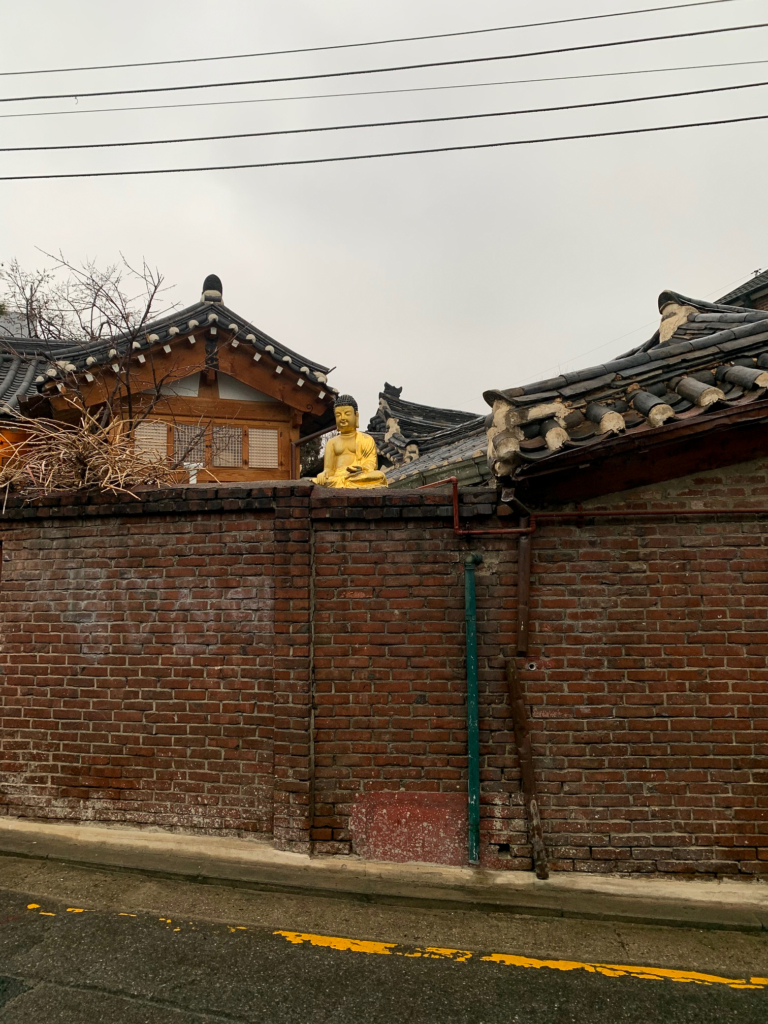 Traditional architecture fence and roofs and a Buddha statue in Bukchon Hanok Village in Seoul