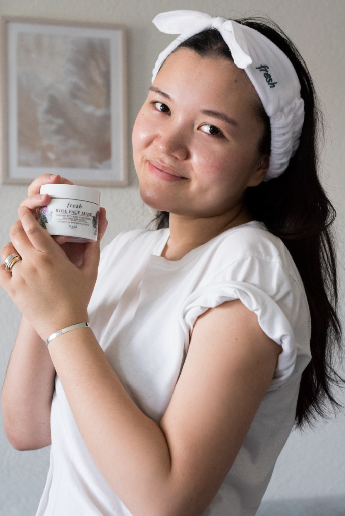 Claire wearing a Fresh headband and holding a jar of rose face mask