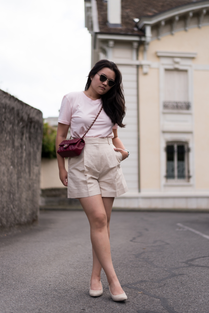 Claire's outfit of the day with cream high-waisted shorts, light pink t-shirt, beige kitten heels, a Chanel mini handbag and sunglasses