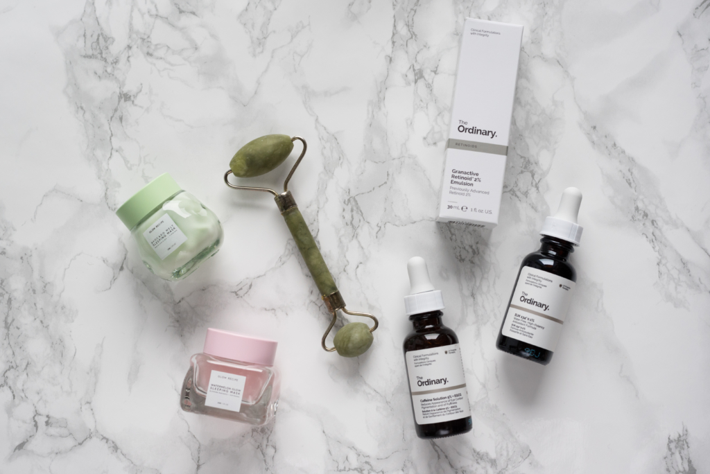 Flatlay of cosmetics products by The Ordinary and Glow Recipe