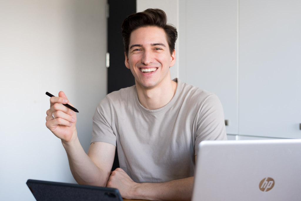 Nicolas smiling and working on his tablet