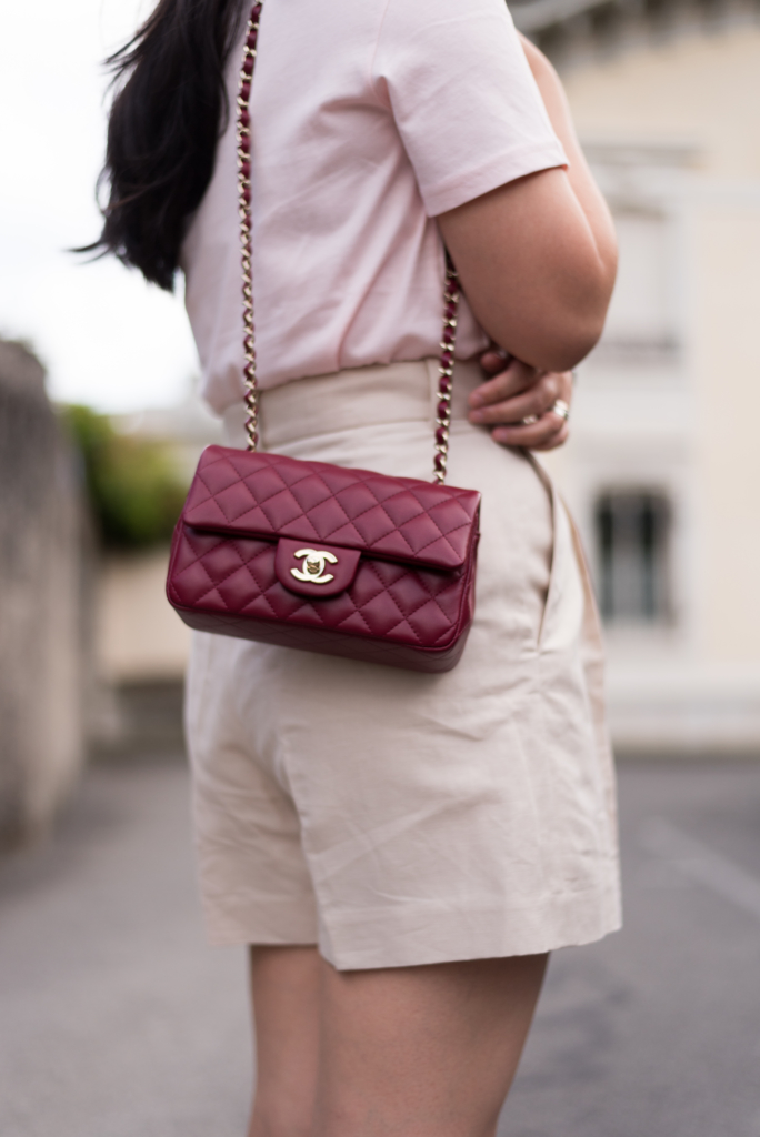 Detail shot of the Chanel mini handbag in burgundy colour with light gold hardware